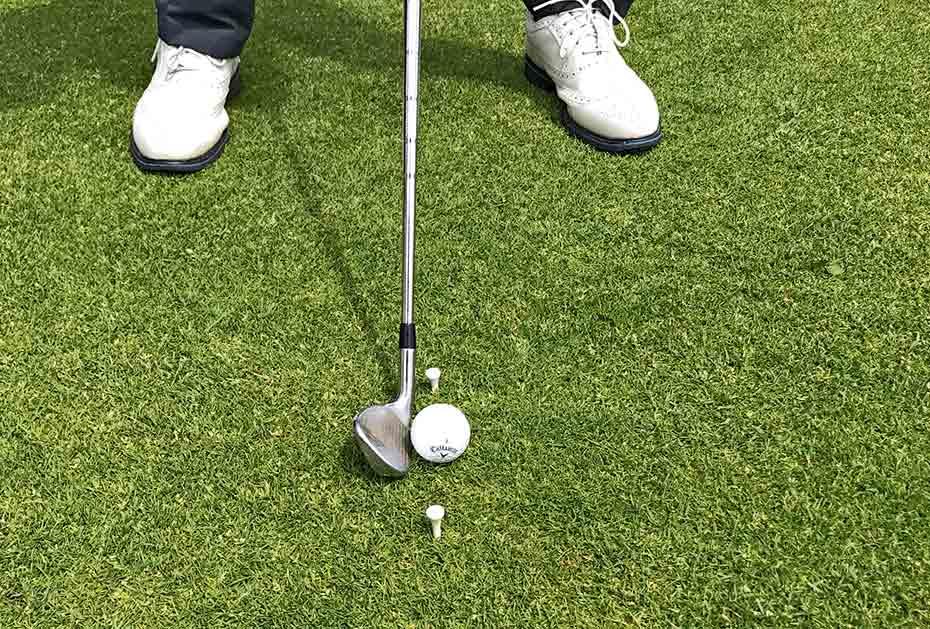 Trainingshilfe: Stecken Sie zwei Tees vor und hinter den Ball (von der Ansprechposition aus betrachtet).