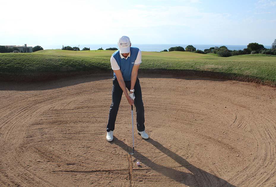 Im Bunker: Richten Sie sich wie gewohnt aus und zeichnen Sie dann eine Linie in Richtung Fahne und zusätzlich eine Linie (zwei bis drei Finger breit) neben dem Ball in den Sand.